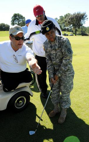 Marty Ebel instructs Sgt. Jameka Promise of the Orlando Warrior Transition Unit during an Army Family and Morale, Welfare and Recreation Command golf clinic Nov. 9 at Walt Disney World by Flickr user familymwr
