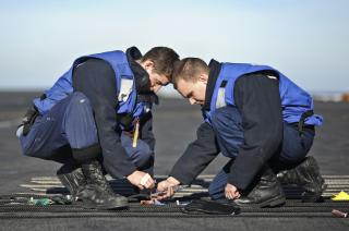 Sailors replace the chemical lights on a phone and distance line. by Flickr user Official U.S. Navy Imagery